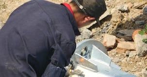 4k de arbeiders die van China en in bouwterrein malen lassen stock video