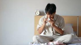 4K De Aziatische mens in pyjama's heeft snot van allergisch gebruikend papieren zakdoekje om het slijm af te vegen, zittend op he stock videobeelden