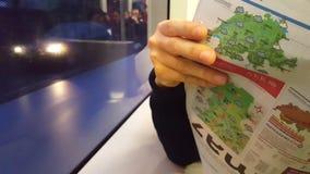 4K de dichte omhooggaande video van UHD van de krant van de ochtendlezing in metropolitaanse tram stock video
