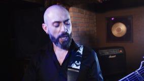 4k de gitarist in zwart overhemd speelt gitaar en zingt  Sluit omhoog mening stock video