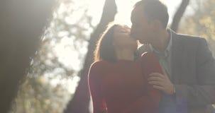 4K De herfst vibes De man koestert erachter vrouwenofferte van en kust haar die zich in het de herfstpark bevinden met gouden bla stock footage