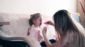 4k: De jonge aantrekkelijke moeder en de zoete dochter spelen de rol van arts en patiënt stock videobeelden