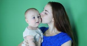 4k - De jonge moeder in blauwe kleding kust een leuke 6 maand oude baby in langzame motie stock video