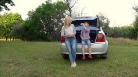 4k de jonge vrouw en haar zoon zitten in de boomstam van een auto reis concept stock footage