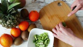 4k de la mujer da la fruta de kiwi del corte con el cuchillo en el tablero de madera, visión superior almacen de metraje de vídeo