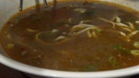 4K de mensen die stokken gebruiken voor eten traditionele rundvleesnoedels in Aziatisch restaurant stock video