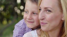 4K de moeder en de zoon koesteren in een park stock video