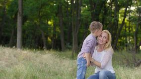 4K de moeder en de zoon zijn in het park en de zoon kust zijn moeder stock videobeelden