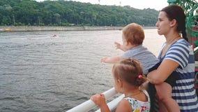 4K De moeder met twee kinderen drijft op een boot op de brede rivier van Dnieper en kijkt overboord stock video