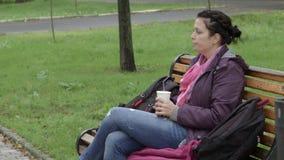 4K de mooie vrouw zit op de parkbank en drinkt latte Zij mengt de drank en blijft drinken stock video