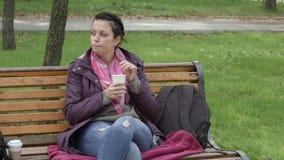 4K de mooie vrouw zit op de de parkbank en het drinken koffie Langzame Motie stock videobeelden