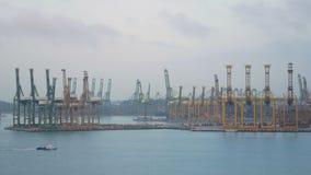 4K De verschepende haven van Singapore met vrachtschip die langzaam op het overzees en vele container en gele kranen op achtergro stock footage
