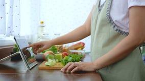4K De de vingerdia van het vrouwengebruik op het tabletscherm en snijdende verse sla, bereidt ingrediënten voor het koken voor vo stock video