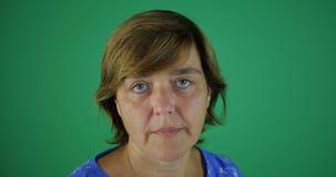 4k - De vrouw op middelbare leeftijd kijkt ernstig en knipoogt, het groene scherm, langzame motie stock videobeelden