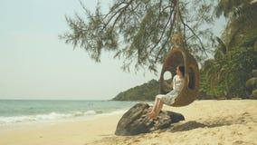 4K de vrouw vindt ontspan, spelend schommeling onder de boom op het strand in vrije tijd tijdens de vakantie van de de zomervakan stock video
