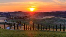 4K de zonsondergang van de tijdtijdspanne over de rollende heuvels en de windende weg in Toscanië, Italië stock video