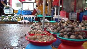 4K de Zuidkoreaanse Verkoper verkoopt Tweekleppige schelpdieren in de Jagalchi-Vissenmarkt in Busan stock video