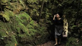 4k defile from the forest stone cave moss covered in black handmade skirt squares textures, deep in the green forest in. Sunglasses , black long sleeves shirt stock footage