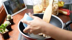 4K den kvinnliga handen satte räkan i en panna, och uppståndelse, förbereder ingredienser för att laga mat följer laga mat nöjt l