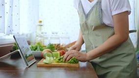 4K den kvinnliga handen som skivar ny grönsallat, förbereder ingredienser för att laga mat följa att laga mat online-videogemet p