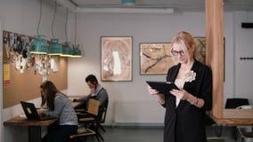 4K den unga härliga blonda affärskvinnan använder en pekskärmminnestavla i det moderna startup kontoret royaltyfri bild