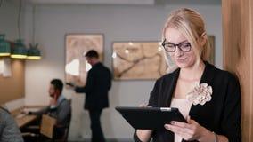 4K den unga härliga blonda affärskvinnan använder en pekskärmminnestavla i det moderna startup kontoret Royaltyfria Bilder