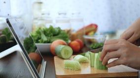 4K det kvinnliga handsnittet och skivagurkan, förbereder ingredienser för att laga mat följa att laga mat online-videogemet på we