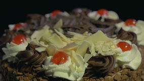 4k - Detail of a delicious chocolate cake spinning on a black background stock footage