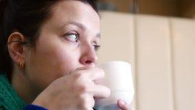 4K dichte omhoog geschotene vrij jonge vrouwenzitting bij koffie het drinken thee het opwarmen stock footage