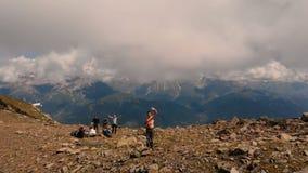 4k - Die Freunde, die in den Bergen, wellenartig bewegendes hallo, Luftaktion wandern stock footage