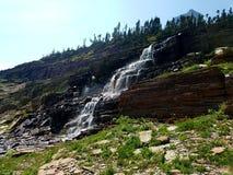 4k, die hohen Gletscher Rocky Mountains überraschen, strömen Wasserfall im Sommer Lizenzfreie Stockfotografie