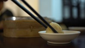 4K Dipping dumpling into soy sauce in restaurant. Traditional chinese food. 4K Dipping dumpling into soy sauce in a restaurant. Eat the hot traditional chinese stock footage