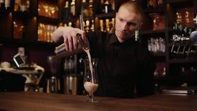 4K disparou de um barman em uma barra exterior derrama um cocktail em uns vidros vídeos de arquivo