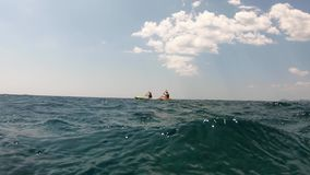 4K Dois pessoas que remam em um caiaque ou em uma canoa no mar de adriático Vista da ?gua filme