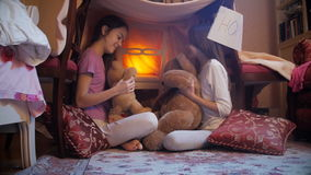 4k dolly shot of two sister playing with teddy bears on floor at bedroom stock footage