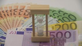 4K Dolly sliding of sand hourglass with euros banknotes of different values. 4K Dolly sliding shot of sand hourglass with euros banknotes of different values stock footage