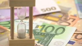 4K Dolly sliding of sand hourglass with euros banknotes of different values. 4K Dolly sliding shot of sand hourglass with euros banknotes of different values stock video