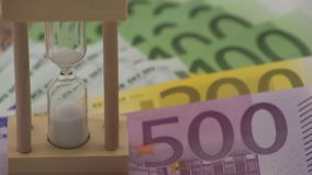 4K Dolly sliding of sand hourglass with euros banknotes of different values. 4K Dolly sliding shot of sand hourglass with euros banknotes of different values stock video footage