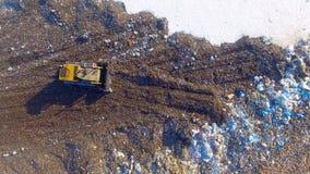 4K Dozer bulldozer som arbetar på avskrädeförrådsplatsen Direkt från över Antennskott arkivfilmer