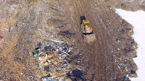 4K Dozer bulldozer som arbetar på avskrädeförrådsplatsen Direkt från över Antennskott stock video