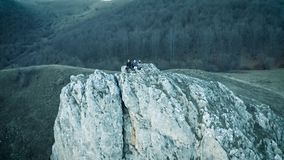 4k drone aerial. Hiking young people sitting on a cliff stock footage