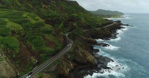 4K Drone Coastal Roadway Rocky Shore Crashing Waves Mountainside Flying Backwards stock footage