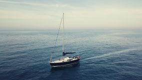 4k orbit aerial of sailing boat in sunset cloudscape stock video footage