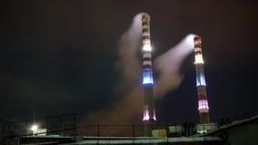 4k Dwa dymienia fabryki ogromne drymby iluminować przy nocą Przemysł, manufaktury timelapse zbiory wideo