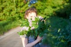 K?dzierzawa dziewczyna z bukietem bez na naturze na letnim dniu zdjęcia stock