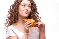 Kędzierzawa kobieta je croissant Zdjęcie Royalty Free