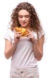 Kędzierzawa kobieta je croissant Zdjęcie Stock