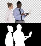 Удовлетворенный их человека и женщины работы смотря в ноутбуке, канал альфы стоковая фотография rf
