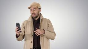 Молодой человек звоня видео- из его мобильного телефона пока идущ на предпосылке градиента стоковая фотография