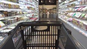 4K een Aziatische supermarkt met producten op de planken Het winkelen met Karretje stock footage